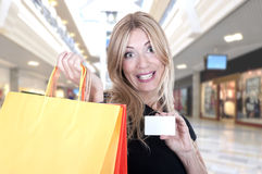 Smiling blonde in shop with bags Stock Photos