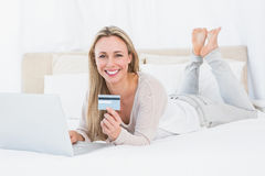 Smiling blonde shopping online on the bed Stock Photo