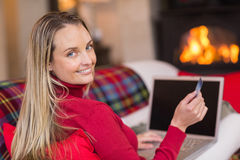 Smiling blonde shopping online with laptop at christmas Stock Photos