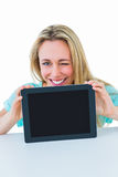 Smiling blonde showing tablet and winking Royalty Free Stock Images