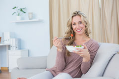 Smiling blonde sitting on couch eating salad Stock Images