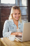 Smiling blonde sitting and typing on laptop Royalty Free Stock Photography