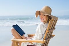 Smiling blonde sitting on wooden deck chair by the sea using tablet Stock Image