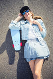 Smiling blonde skater lying on the highway Stock Photography