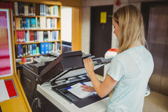 Smiling blonde student making a copy. In library Royalty Free Stock Images