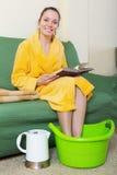 Smiling blonde taking foot bath Stock Image