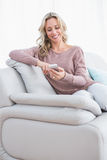 Smiling blonde text messaging on the couch. At home in the living room royalty free stock photos