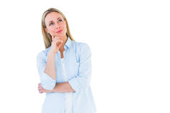 Smiling blonde thinking with hand on chin Stock Photo