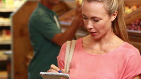 Smiling blonde ticking off grocery list. Portrait of smiling blonde ticking off grocery list in grocery store stock video