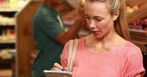 Smiling blonde ticking off grocery list. Portrait of smiling blonde ticking off grocery list in grocery store stock footage