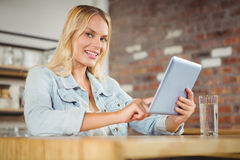 Smiling blonde touching on tablet computer Stock Photo