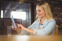 Smiling blonde touching on tablet computer. At coffee shop Stock Photography