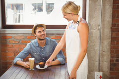 Smiling blonde waitress serving muffin to handsome hipster Stock Images