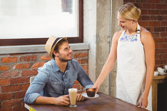 Smiling blonde waitress serving muffin to handsome hipster Royalty Free Stock Photography