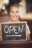 Smiling blonde waitress showing chalkboard with open sign Stock Photography