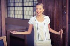 Smiling blonde waitress welcoming Royalty Free Stock Image