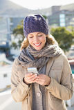 Smiling blonde in warm clothes text messaging Royalty Free Stock Photo