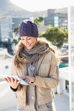 Smiling blonde in warm clothes using tablet Royalty Free Stock Photos