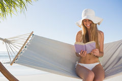 Smiling blonde wearing sunhat sitting on hammock reading book Stock Image