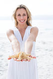 Smiling blonde in white dress holding starfish Stock Photos