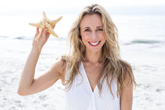 Smiling blonde in white dress holding starfish Royalty Free Stock Image