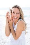 Smiling blonde in white dress listening the seashell Royalty Free Stock Photos