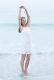Smiling blonde in white dress standing by the sea Stock Images