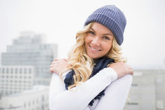 Smiling blonde in winter clothes posing outdoors Royalty Free Stock Image