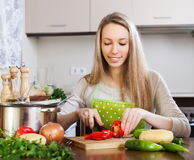 Smiling blonde woman in apron slicing  pepper Royalty Free Stock Images