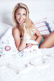 Smiling blonde woman in bed Royalty Free Stock Image