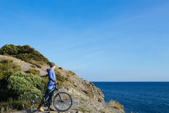 Smiling blonde woman with the bike is standing on a rock and looking at the sea. Attractive young smiling blonde woman with the bike is standing on a rock and Stock Image