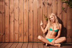 Smiling blonde woman in bikini sitting and showing thumb up Royalty Free Stock Image