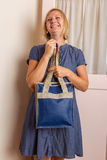 Smiling Blonde Woman With Blue Leather Purse Stock Photo