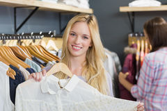 Smiling blonde woman choosing clothes and looking at camera Stock Image