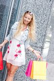 Smiling blonde woman with colorful bags on shopping tour Royalty Free Stock Photography