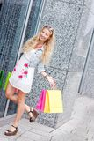 Smiling blonde woman with colorful bags on shopping tour Royalty Free Stock Image