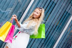 Smiling blonde woman with colorful bags on shopping tour Stock Photography