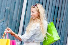 Smiling blonde woman with colorful bags on shopping tour Stock Image