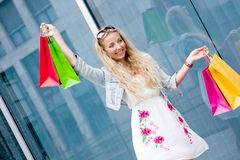 Smiling blonde woman with colorful bags on shopping tour. In the city outdoor Royalty Free Stock Photo