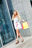 Smiling blonde woman with colorful bags on shopping tour Royalty Free Stock Images