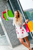 Smiling blonde woman with colorful bags on shopping tour. In the city outdoor Stock Images