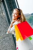 Smiling blonde woman with colorful bags on shopping tour Stock Photos