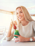 Smiling blonde woman with cooling cocktail in sunny cafe Royalty Free Stock Photography