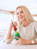 Smiling blonde woman with cooling cocktail in sunny cafe Royalty Free Stock Images