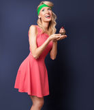 Smiling blonde woman with cupcake. Royalty Free Stock Images