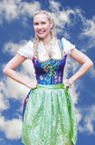Smiling blonde woman in dirndl in front of blue sky. Happy blonde woman in dirndl in front of blue sky royalty free stock photo