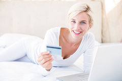 Smiling blonde woman doing online shopping Royalty Free Stock Photo