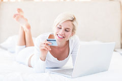 Smiling blonde woman doing online shopping Royalty Free Stock Images
