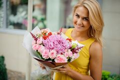 Smiling blonde woman dressed in a yellow dress holding a pink bouquet of flowers Royalty Free Stock Images