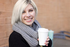 Smiling blonde woman drinking coffee outdoor at cafe Stock Photos